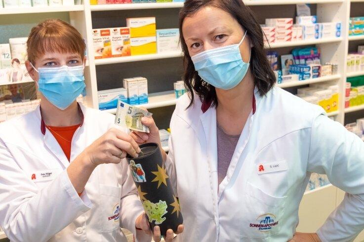 Marlies Tröger (links) und Sandra Lazic präsentieren in der Sonnen-Apotheke die Spendenbox für die Sternsinger-Aktion.