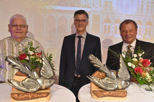 Dieter Heyne (rechts) und Peter Nicolaus (links) haben von Bürgermeister Olaf Schlott die Große Elster überreicht bekommen. Die Stadt würdigt damit jahrelanges Engagement im Ehrenamt.