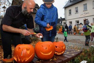 """Alexander Schnerrer (links), Inhaber der Gaststätte """"Zur Börse"""", freute sich über die große Resonanz zum 1. Zwönitzer Kürbisschnitzen. Auch Lenny Rehm schaute mit seiner Familie vorbei."""