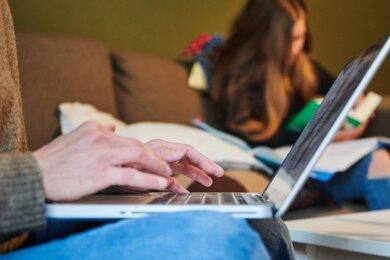 Während die Mutter auf dem Sofa am Laptop arbeitet, erledigt die Tochter ihre schulischen Aufgaben. Wie sie die Zeit des Homeschooling erlebte, hat eine Schülerin aufgeschrieben.