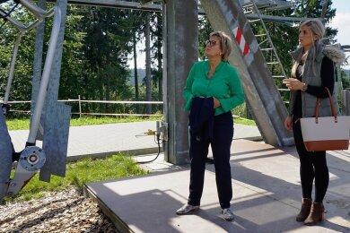 Staatsministerin Barbara Klepsch (links) lässt sich von DLT-Geschäftsführerin Jennifer Braun die Sommernutzung des Vierer-Sessellifts für die Bikewelterklären.