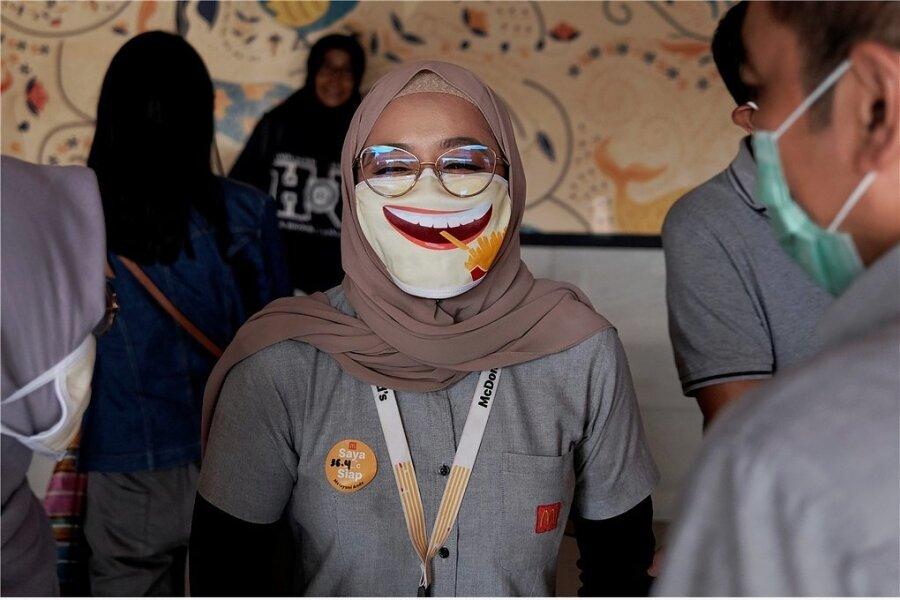 Humor in der Krise kann auch helfen: Die Mitarbeiterin eines Schnellrestaurants in Indonesien trägt einen Mundschutz mit Lach-Motiv.