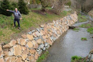 Volkmar Roth steht am abschüssigen Ufer des Raumbachs. So hat er sich seinen Garten nicht vorgestellt.