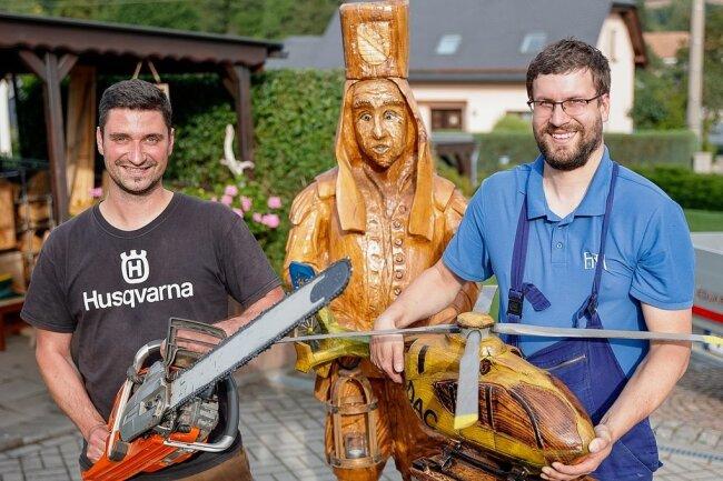 Mathias Kämpfer (links) hat schon etliche Kunstwerke per Kettensäge gezaubert - darunter den Bergmann (hinten) und das Modell des ADAC-Hubschraubers, den hier Muldenbergs Ortswehrchef Nils Golla hält.
