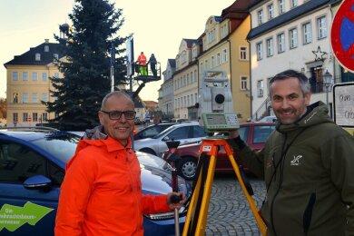 Detlef Wuttke (l.) mit Reflektorstab und Alexander Neumeister am Stativ mit Tachymeter sind als Weihnachtsbaum-Vermesser unterwegs, hier auf dem Markt in Hainichen.