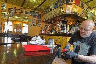 """Johannes Gerhardt, Wirt der Hohenstein-Ernstthaler Gaststätte """"Apfeltraum"""", nutzt die Corona-Zeit für kleinere Reparaturen, etwas das Lackieren der Tische. Der Frontmann, Gitarrist und Sänger der Kultband RB II denkt entgegen kursierender Gerüchte noch lange nicht ans Aufgeben."""