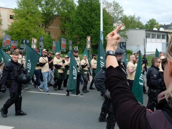 """Teilnehmer eines rechten Aufmarsches der Partei """"Der dritte Weg"""" sind zu sehen. Eine Demonstrantin protestiert."""