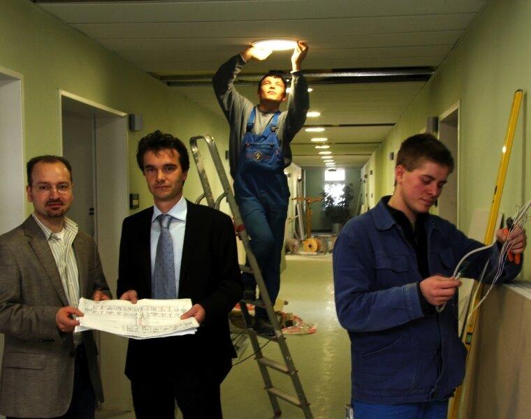 """<p class=""""artikelinhalt"""">Jan Wetzel (l.) ist der neue Leiter des Pflegeheims, das derzeit im Marienstift Schwarzenberg entsteht, hier im Gespräch mit EKH-Geschäftsführer Thoralf Bode. Elektriker David Lange und Tobias Schmidt (r.) von der Firma Schramm & Lorenz verkabeln die Lampen auf dem Flur im Obergeschoss.</p>"""