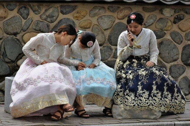 Tradition trifft Moderne: Junge Mädchen im Hanbok, der typischen koreanischen Tracht.