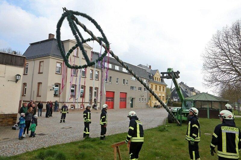 1. Mai 2021: Wenige Gäste verfolgen das Aufstellen des Maibaums mit einem Kran.