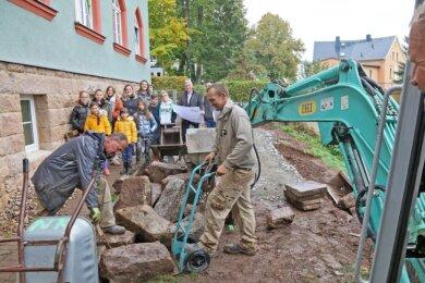 Gespannt verfolgen die Kinder und Jugendlichen der Wohngruppe des Zwickauer Kinderhaus-Vereins die Bauarbeiten hinter der grünen Villa in Planitz. Der Hang wird derzeit von der Firma Gala-Bau zu einem Garten mit Terrasse umgestaltet.
