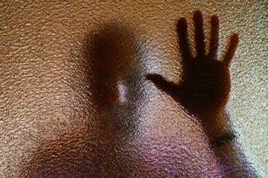 Ein Mann hinter einer Glasscheibe (Symbolbild). Opfer von Stalkern stehen oft unter hohem psychischem Druck.
