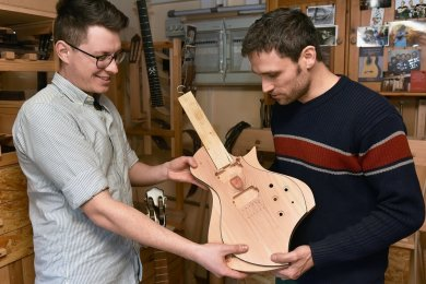 In der Oelsnitzer Gitarrenbauwerkstatt Odem entstehen E-Gitarren aus Holz, das aus Sicht des Burgstädter Designers Tim Walter (links) und Instrumentenbaumeisters Roy Fankhänel (rechts) mit Makeln behaftet sein darf. In einem Fall wird das Astloch im Holz gestalterisch aufgegriffen.