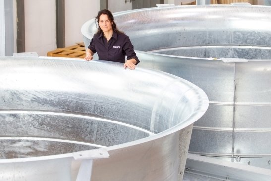 Mitarbeiterin Antje Keßler zeigt die Ventilatorengehäuse, die Teil einer großen Wärmetauscher-Anlage werden. Sie geht nach Dänemark.