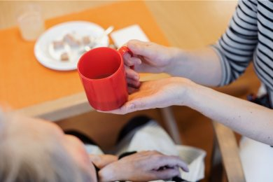 """Eine Pflegerin reicht einer Frau in einem Pflegeheim ein Getränk. Der Bundestag hat am Freitag eine Pflegereform beschlossen. Der Chemnitzer Unternehmer Sebastian Thieswald nennt sie einen """"Schnellschuss""""."""