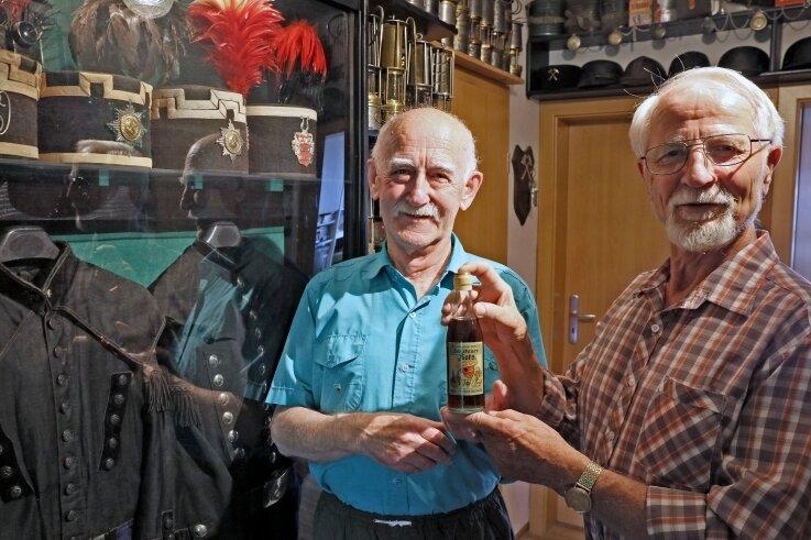 """Werner Gottschald (76, rechts) schenkt Jürgen Schlosser (77) eine Flasche """"Zwickauer Koks"""", die vermutlich aus dem Jahr 1949 stammt."""