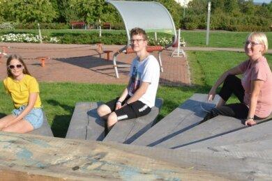 Elisa, Immanuel und Kerstin (von links) haben die neue Sitzgelegenheit im Lugauer Stadtpark schon getestet.