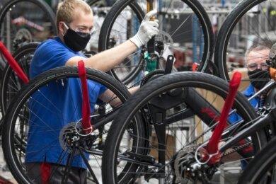 Mitarbeiter des Fahrradherstellers Diamant montieren Elektro-Trekkingräder an einer Linie im Werk in Hartmannsdorf. Unter Einhaltung von Mindestabständen und weiteren Hygienemaßnahmen, wie dem Tragen eines Mund-Nasen-Schutzes, läuft die Produktion in der Coronakrise.