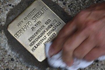 Ein Stolperstein an der Brückenstraße in Chemnitz wird gereinigt.
