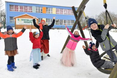 Xenia (6), Paulina (6), Charlotte (7), Nika (6) und Louis (7) (v.l.) von der Kita Naundorf haben mit Leiterin Isabel Garbatz Gaudi im Garten.