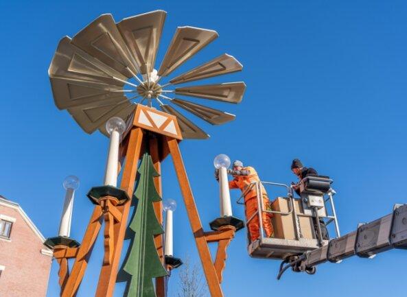 Am Dienstag wurde die etwa acht Meter hohe Pyramide an der Breitscheidstraße aufgebaut. Ihr Metallgestell steckt jetzt in einer Holzverkleidung, auch die Farbgebung ist völlig neu. Im Bild auf der Hebebühne Bauhofmitarbeiter Patrick Schädlich (links) und Marktmeister Jan Gabriel.