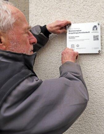 Reiner Hoffmann bringt die Unesco-Plakette am Drei-Brüder-Schacht an.