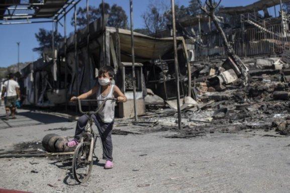 Ein Junge steht vor verbrannten Trümmern in Moria. Dem Großbrand vorangegangen waren Unruhen unter den Migranten, weil das Lager nach einem ersten Corona-Fall unter Quarantäne gestellt worden war.