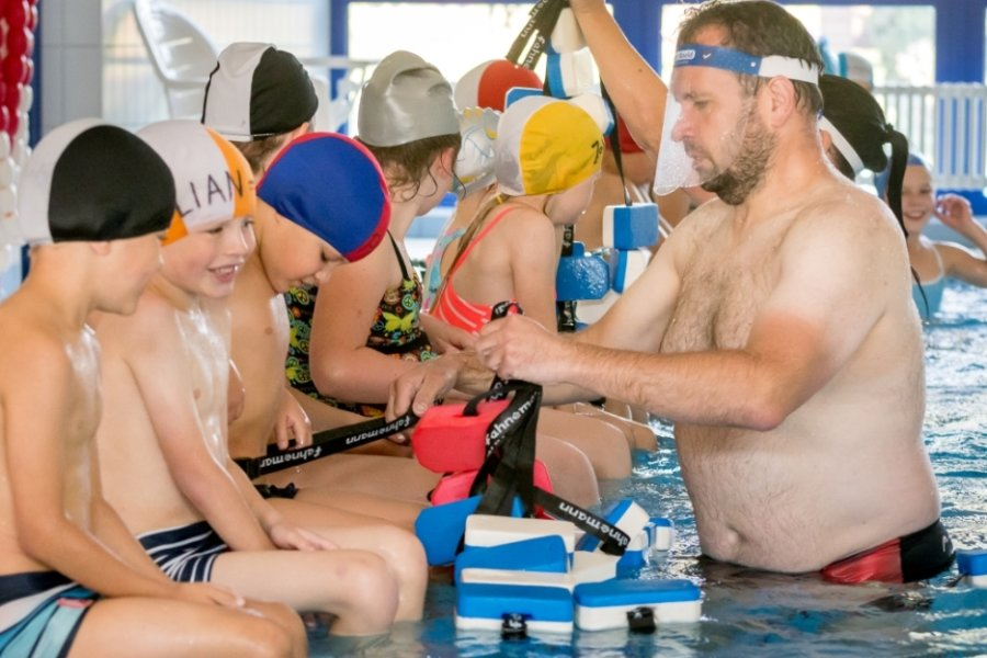 Damit geht es gleich viel leichter: Schwimmtrainer Alexander Steiner legt den Kindern eine Schwimmhilfe um, damit es mit dem Brustschwimmen und dem Seepferdchen auch klappt.