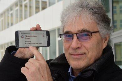 Helmut Geilert zeigt auf dem Smartphone die Internetseite von CB Applications. Der IT-Experte hat gemeinsam mit zwei Partnern eine Software entwickelt, mit der sich Lieferketten optimieren lassen.