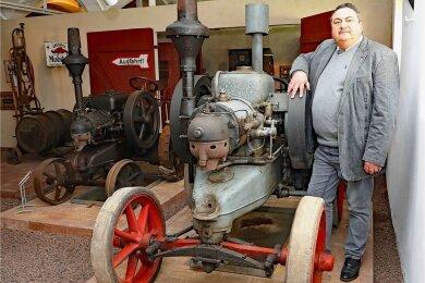 Museumschef Jürgen Knauss an einem Lanz-Modell aus dem Jahr 1921, das unter anderem im Kuhstall des Deutschen Landwirtschaftsmuseums ausgestellt ist. Links steht der sogenannte Eisenmops, Baujahr 1924.