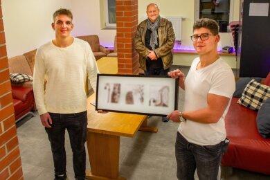 Noch ist der Bilderrahmen nur mit Symbolbildern bestückt. Jonas Leisner (links) und Paul Schatz (rechts) hoffen ebenso wie Thilo Walther, dass der Rahmen bald Bilder von eigenen Aktivitäten trägt.