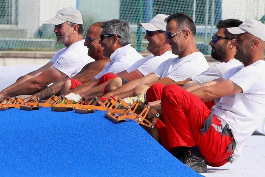 Mit vereinten Kräften und Greifzangen: Die Mitarbeiter eines Sportstättenbau-Unternehmens bringen den Kunstrasenbelag in Position.
