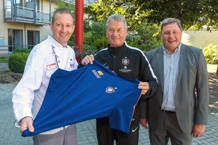 Im Beisein von Verwaltungsleiter Ferdinand Keller überreichte Ex-Fußballer Holger Erler an Küchenchef Erik Günther (v. r.) das Aue-Trikot.