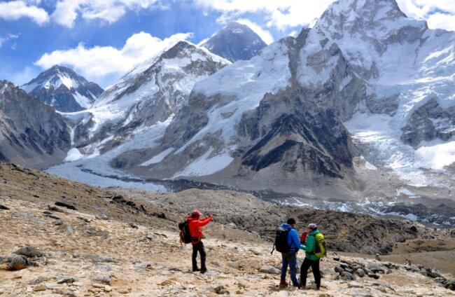 Trekkingtouristen am Aussichtsberg Kala Patthar (5545 m) mit Blick auf die Gipfelpyramide des Mount Everest (Mitte) und den Khumbu-Eisbruch (links).