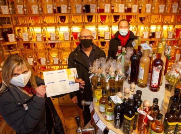 Nicht nur Geschenke flüssigen Inhaltes, aber vor allem diese, können Kunden im Barrique an der Rathausstraße erwerben. Bei Weinhändler Fritz Mandel (Mitte) laufen die Fäden für das Gewinnrätsel zusammen. Gemeinsam mit Gabi Gerold und Eckhard Sorger von der Plauener Wirtschaftsförderung hofft er auf reges Interesse.