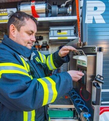 Schwarzenbergs Wehrleiter Lars Wagner nutzt hier das Desinfektionsmittel am Hygieneboard eines Fahrzeugs.