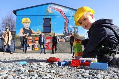 Für den vierjährigen Bennek Wenzel aus Meerane gibt es kein schöneres Spielzeug als Bagger, Radlader, Kran und Kipper. Das machte ihn zum potenziellen Werbeträger für die Fassadengestaltung - ein Gemeinschaftswerk von Baufirma, Künstler, Agentur und Architektin.