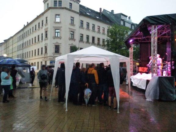 Um sich vor dem Regen zu schützen, stellten Gäste spontan einen Pavillon vor die Bühne.