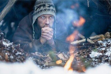 Michael Schubert bei Frost in seiner aus Ästen gebauten Hütte im Erzgebirge.