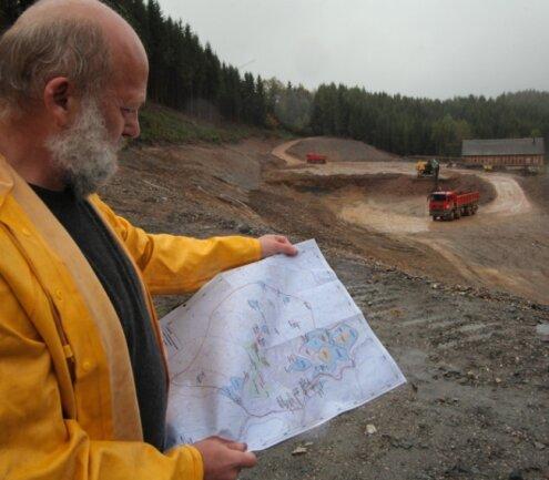 """<p class=""""artikelinhalt"""">Jochen Schreyer vor der Halde mit dem Namen """"Haldenaufbereitung"""". Vor einem Jahr standen hier noch Bäume, die Halde reichte bis an die Straße. Im Zuge der Sanierung werden ihre Böschungen weniger steil gemacht und das Gelände so abgedichtet, dass kein Radon mehr entweichen kann.</p>"""