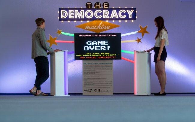 """Benjamin Gruner und Natalie Bleyl vom Pochen-Projekt an der """"Democracy Machine"""" von Adam J. Scarborough, die im September in Chemnitz gezeigt werden soll. """"Game Over - keine Übereinstimmung"""" heißt es auf dem Bildschirm. Ein Selbstläufer ist die Kompromissfindung also nicht."""