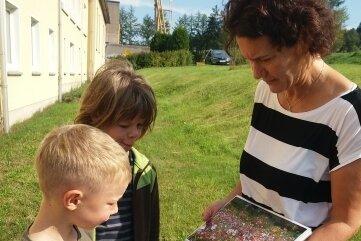 Kita-Leiterin Anke Baumgartner erläutert den Kindern mit Fotos die Sport- und Spielgeräte des neuen Gartens.