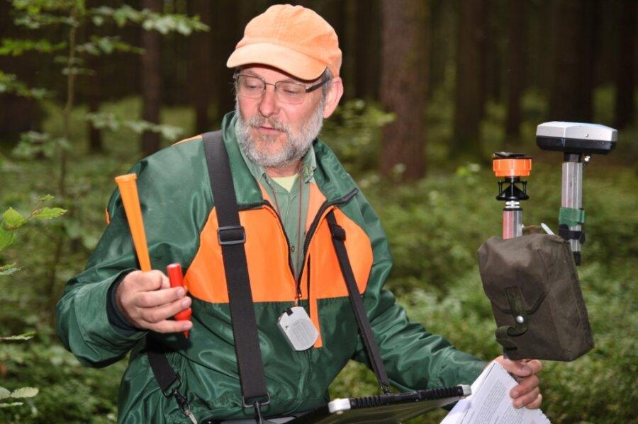 """Forstsachverständiger Volker Marx während der Waldinventur. Der kleine rote Keil (""""Pinocchio"""") markiert den Suchpunkt, der orangefarbene Kegel ist ein optischer Hinweis zum Wiederfinden."""