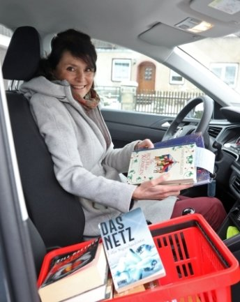 Katrin Hisslinger fährt Bücher der Bibliothek aus.