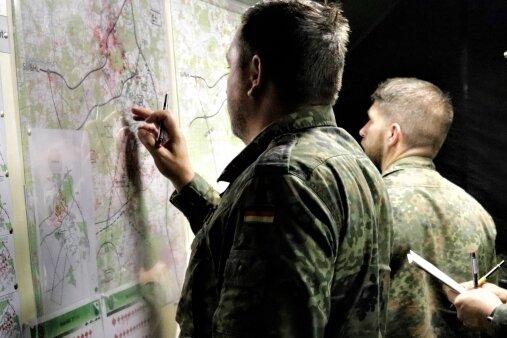 Offiziere besprechen das taktische Vorgehen an der Lagekarte.
