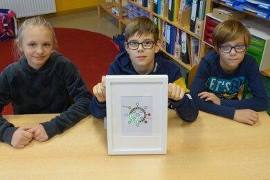 Eine CO2-Ampel zeigt den Viertklässlern Linda Wolter, Fabian Grau (Mitte) und Theodor Frickert in ihrem Klassenzimmer an, wann es Zeit zum Lüften ist.
