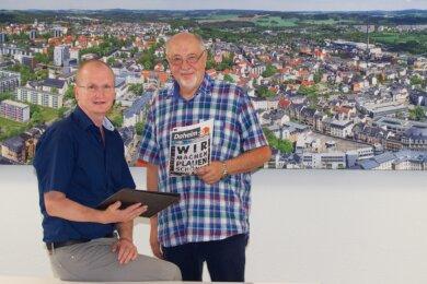 Sie haben Plauen geprägt: WBG-Geschäftsführer Frank Thiele (sitzend) und sein Vorgänger Hellfried Unglaub (bis 2012). Auf dem XXL-Foto hinter beiden sind etliche in 30 Jahren WBG sanierte Häuser zu sehen.