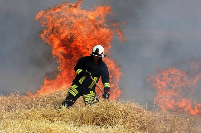 Der Feuerwehrmann versucht, das Stroh vor den immer näher kommenden Flammen wegzuziehen.