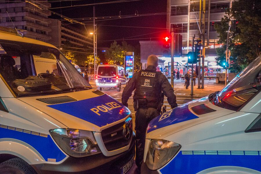 Polizeitransporter werden an der Chemnitzer Brückenstraße so rangiert, dass sie zusätzliche Barrieren auf der anderen Straßenseite bilden, die die Prozessbeteiligten vor unerwünschten Einflüssen von außen abschirmen.