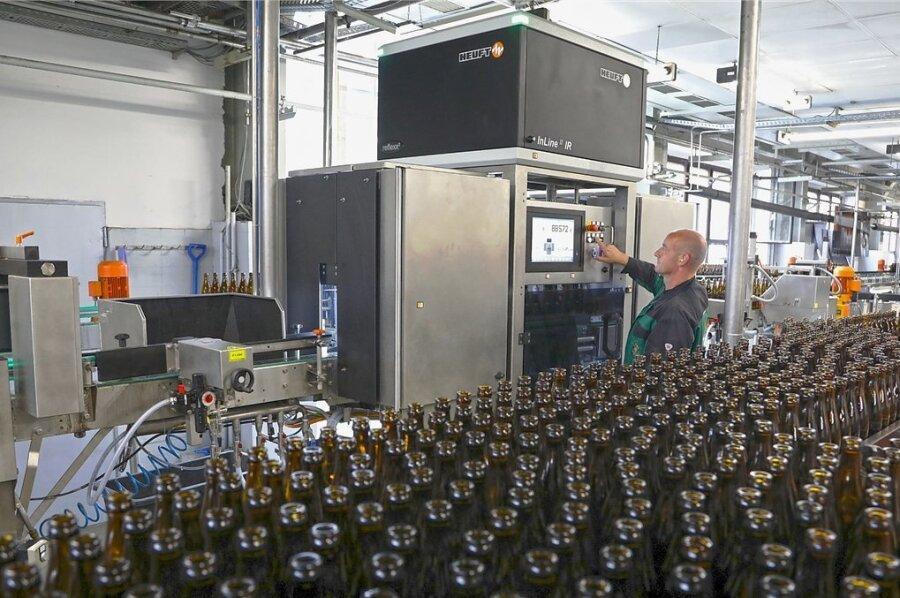 Mitarbeiter Steffen Krämer bedient den neuen Flascheninspektor, der gut 30.000 Mehrwegflaschen pro Stunde vor den Befüllen penibel auf vollständige Sauberkeit, Risse und andere Beschädigungen überprüft.